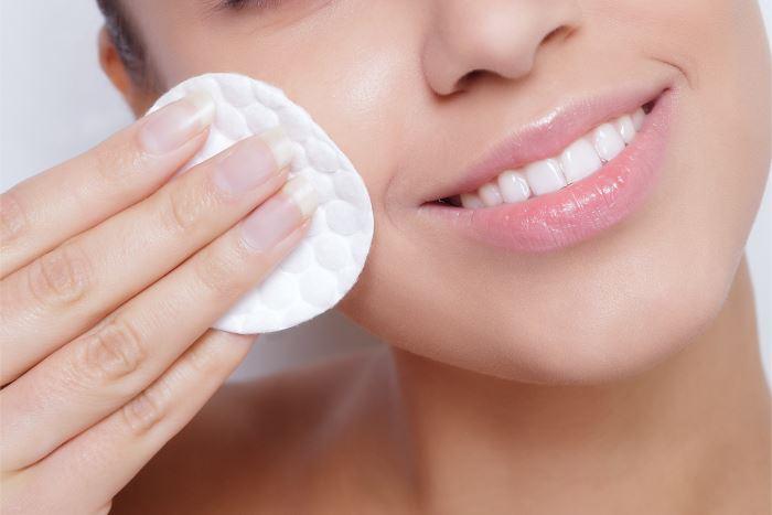 kvinde renser huden i ansigtet med vatrundel mens hun smiler