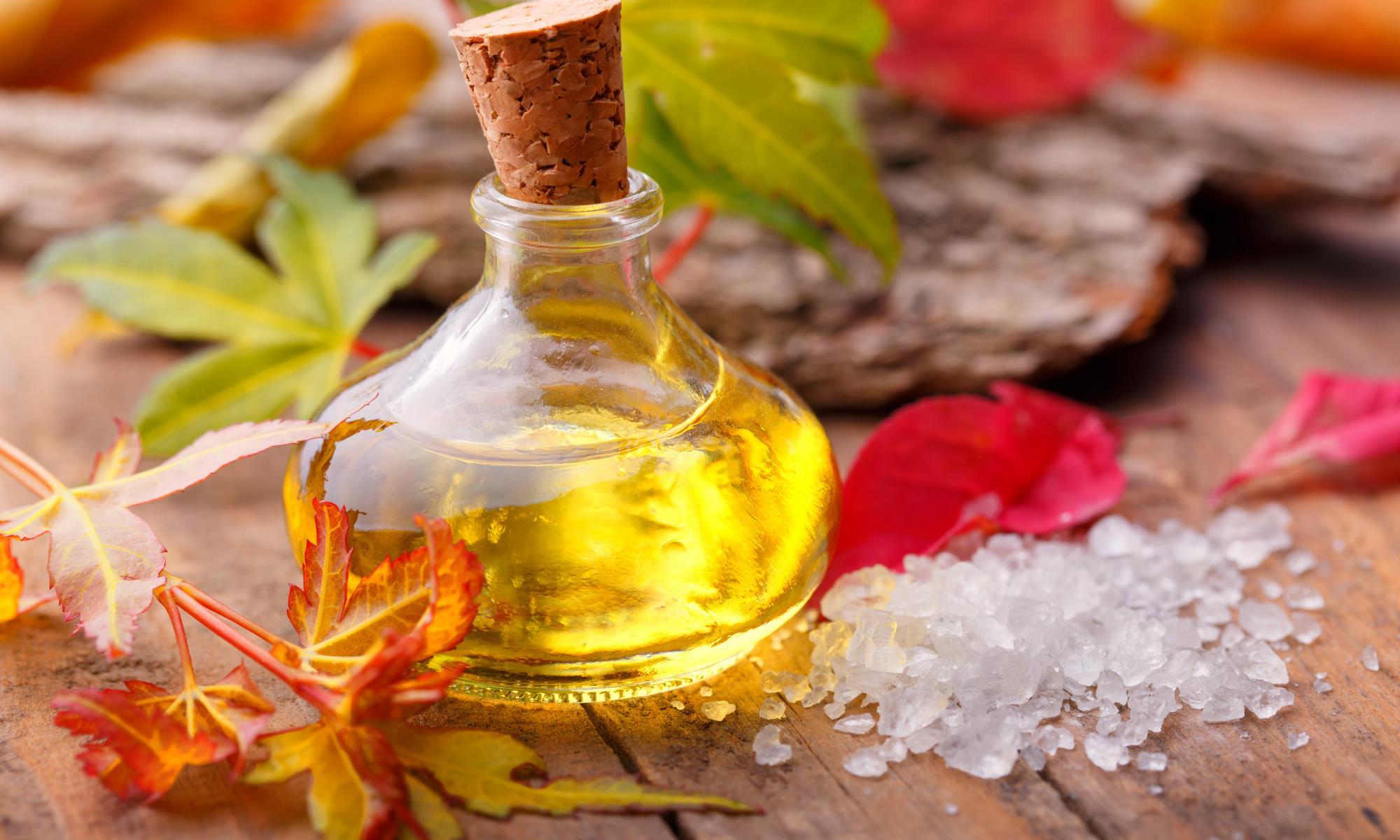 Flaske med olie, korkprop med dødehavssalt og forårsblade