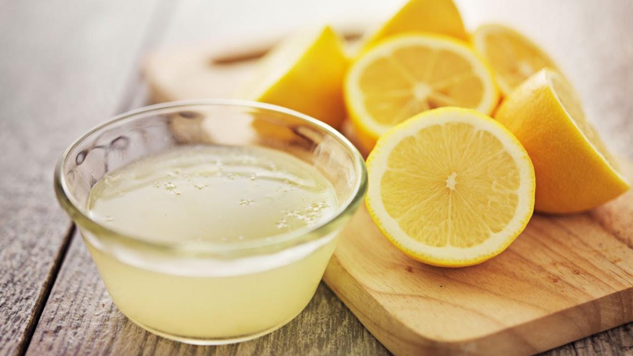 skål med citronsaft og friske skåret citroner på skærebrædt