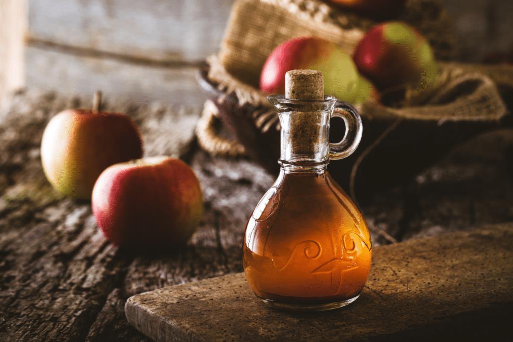 æblecidereddike i fin glas flaske med æbler i baggrunden