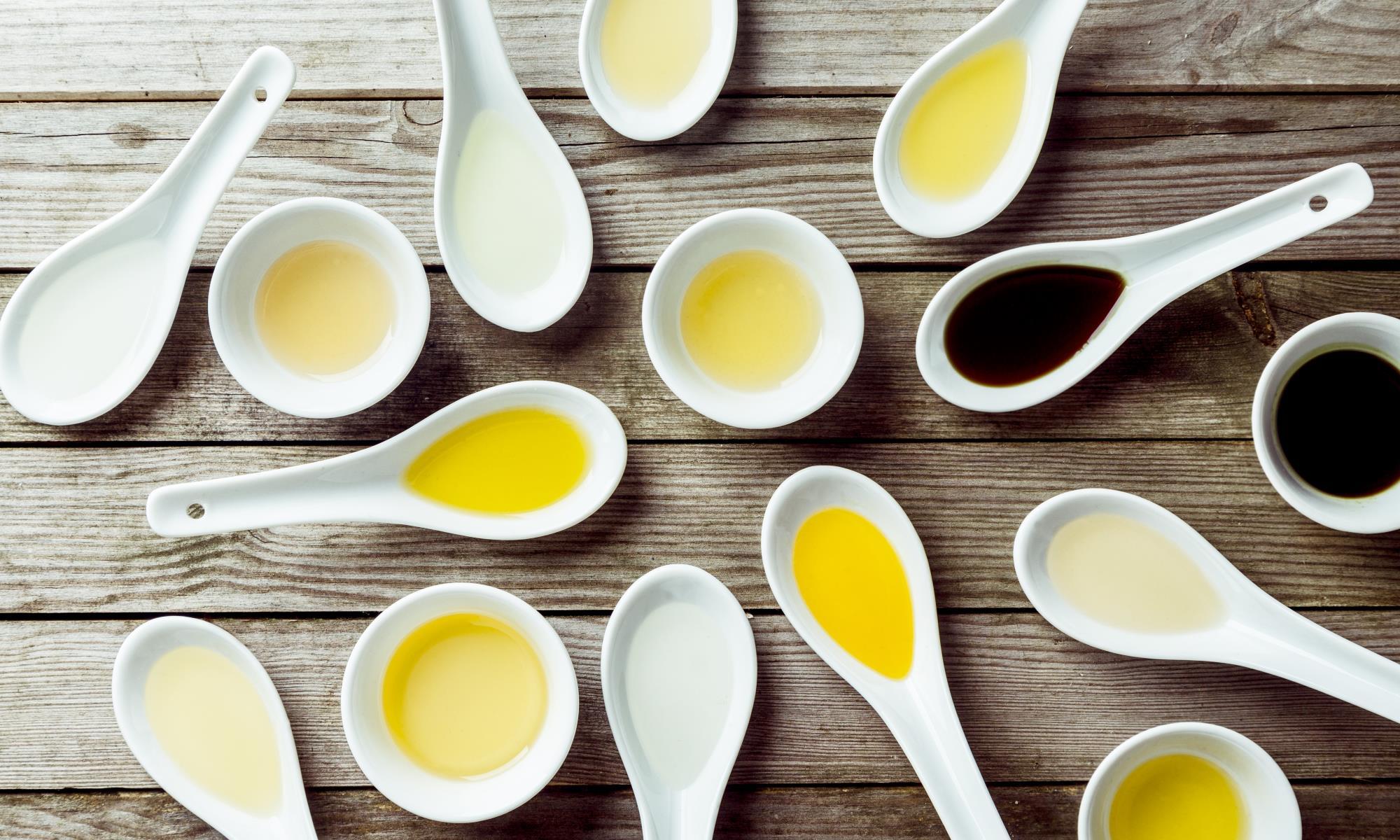 hvilken olie er bedst - træbord med skeer fyldt af gule og mørke olier