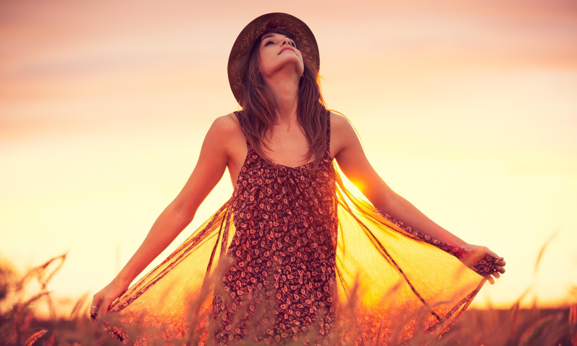 Det rigtige valg af olie - kvinde i marken med solnedgang i baggrunden - hovedet holdt højt mod himlen