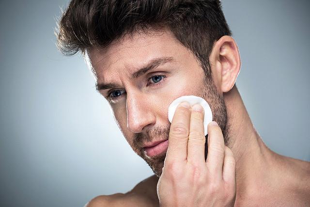 mand med skæg renser huden med vatrondel - skintonic, toner, anisgtsmist